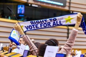 "Una persona con disabilità solleva una sciarpa con la scritta ""Right to Vote for All"" (""Diritto di voto per tutti""."