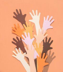 Tante mani di carta di colorazioni diverse tendono verso l'alto a esemplificare una comunanza nelle vicende umane.