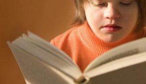 Una giovane persona con sindrome di Down legge un libro.