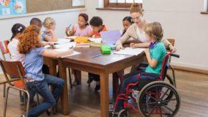 Un gruppo classe composto da diversi/e studenti, di cui una con disabilità motoria, svolge un compito con la supervisione dell'insegnante.